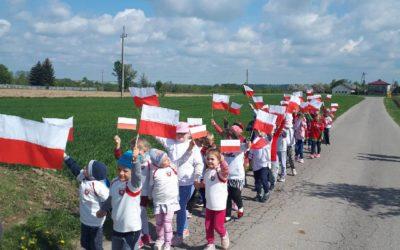 Przemarsz przedszkolaków i uczniów klas I-III z flagami przez Nowy Skoszyn
